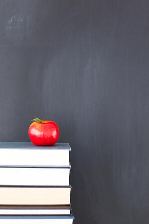 Stack of books with red apple and clean blackboard